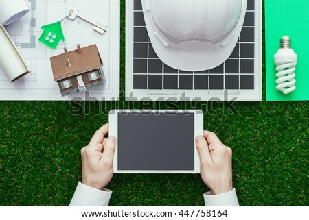 Eco house and sustainable building concept: work tools, solar panel and drafts on the grass, hands holding a digital tablet at center - stock photo