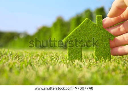 Eco house concept ,hand holding eco house icon in nature - stock photo