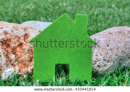 Eco house concept in a green grass and stones, green eco house icon in nature - stock photo