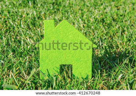 Eco house concept in green grass, green eco house icon in nature - stock photo