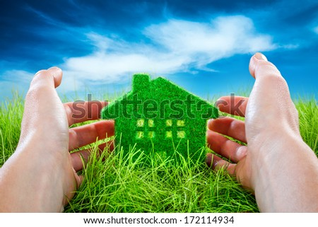 Eco House in green grass protected by the human hands on blue sky background. - stock photo