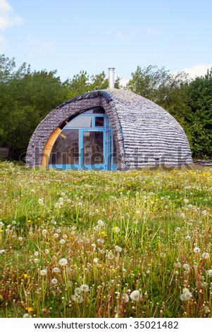 eco house made from recycle materials. environmentally friendly home in a field
