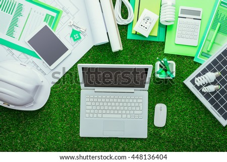 Eco house projects, work tools and solar panel on the grass, laptop at center, green building and energy saving concept - stock photo