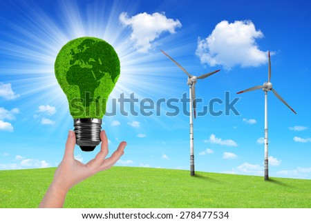 Eco Light bulb in hand in the background wind turbines - stock photo