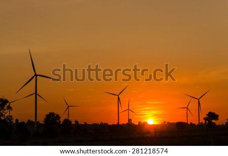 Eco power in wind turbine farm with sunset. - stock photo
