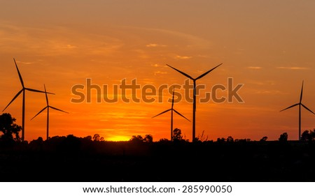 Eco power in wind turbine farm with sunset - stock photo