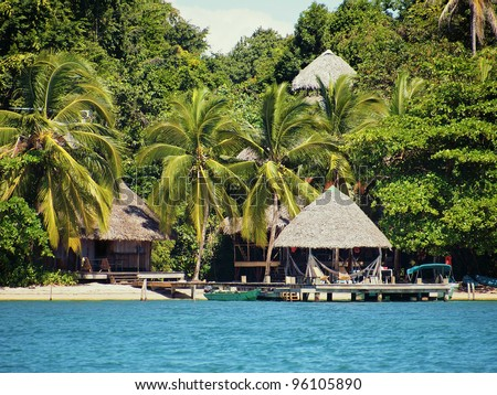 Eco resort on a Caribbean beach with thatched huts and lush tropical vegetation, Bocas del Toro, Panama - stock photo