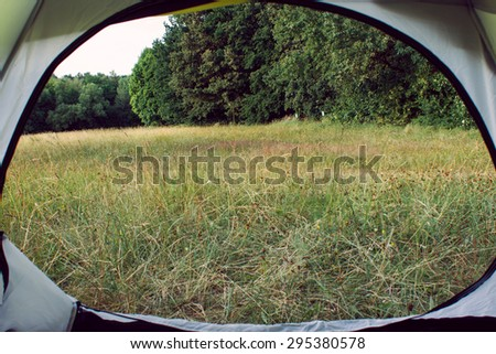 Eco tourism. Photo made from the tent in the field near the forest - stock photo
