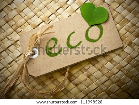 eco word written onto a cardboard label, green clover leaf, brown background - stock photo