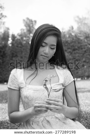 Ecocide and environment concept, Beautiful young asian girl holding dry leaves in her hands - stock photo