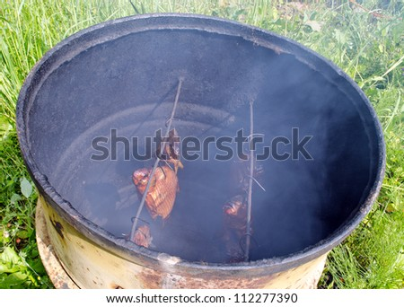 Ecologic fish smoke in smokehouse made of old rusty barrel. - stock photo
