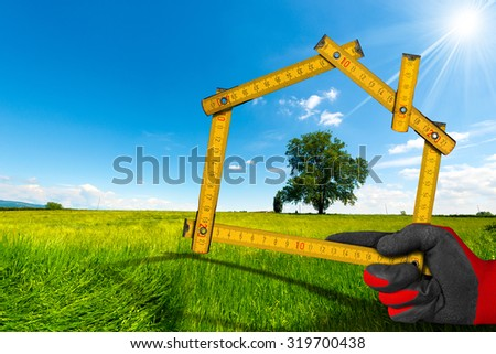 Ecologic House in the Countryside - Project / Hand with work glove holding a wooden meter ruler in the shape of house, in the countryside with green tree. Concept of ecological house project  - stock photo