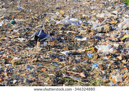 Ecological catastrophe - Trash dump on agricultural field - stock photo