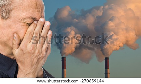 Ecological concept. Elderly man with a face closed by hands against the background of pipes polluting an atmosphere