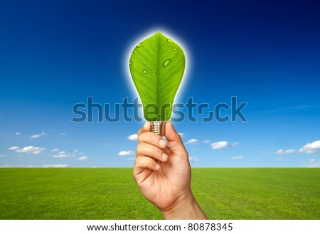 Ecological concept, leaf and lamp mixed together with hand - stock photo