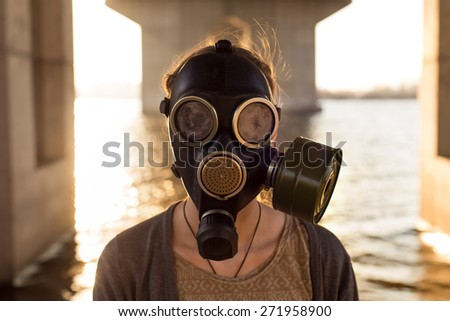 Ecological concept of air contamination. Portrait of woman in gas mask near water