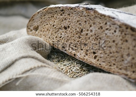 Ecological product. The cut loaf of bread lying on a sack of grain