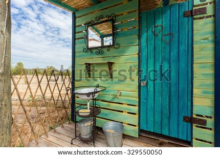 Ecological wooden toilet on the street. The original design and decoration. - stock photo