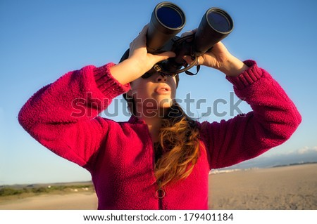 Ecologist young woman watching the environment with binoculars. Wide angle of view - stock photo