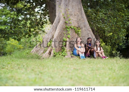 Ecology and sustainability: portrait of three young girls smiling and looking at camera while sitting near big tree in park. Copy space - stock photo
