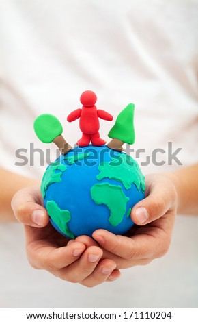 Ecology concept - child hands holding clay world globe with trees and people - stock photo