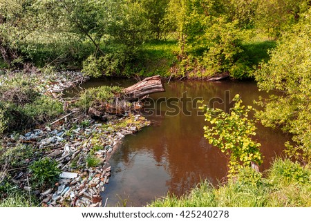 ecology concept. small river, water pollution, empty plastic bottles. River that is polluted with various garbage and trash, Polluted rivers, - stock photo