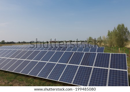 Ecology electric energy farm with solar panel battery in green field and modern solar panels in a beautiful green field