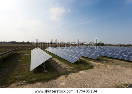 Ecology electric energy farm with solar panel battery in green field and modern solar panels in a beautiful green field  - stock photo