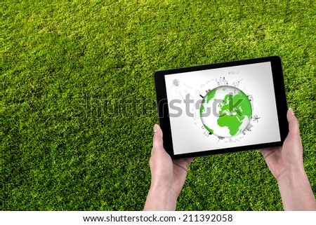 Ecology screen tablet and grass in the background - stock photo