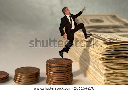 Economic and stock market success concept showing man jumping from coins to cash which represents moving up in the financial world. - stock photo