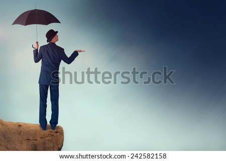 economic forecast outlook concept businessman with umbrella  - stock photo