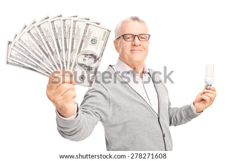 Economic senior holding an energy efficient light bulb and a stack of money isolated on white background - stock photo