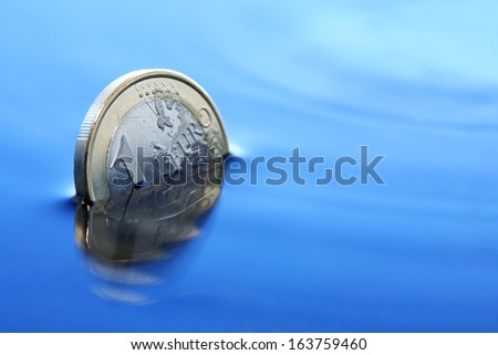 Economy crisis concept. Closeup of one euro coin sinking in water - stock photo