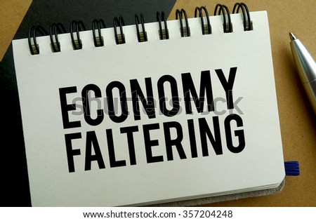 Economy faltering memo written on a notebook with pen