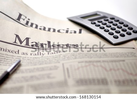 Economy newspaper with calculator in shallow depth of field - stock photo