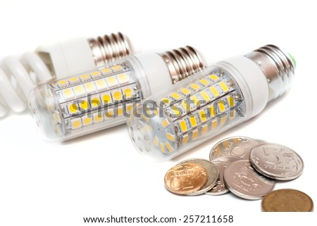 economy of energy. Close-up LED Bulb isolated on white with money