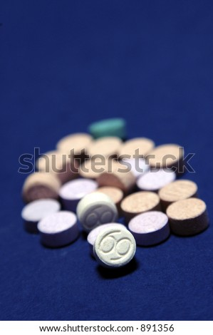 Ecstasy tablets on blue background - stock photo