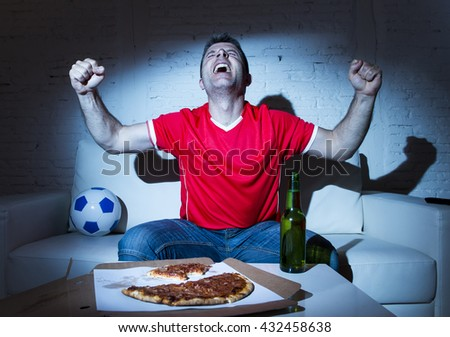 ecstatic and fanatic football fan man watching soccer game on television in red team jersey celebrating goal crazy happy on  couch at home with ball and  beer bottle eating pizza dark light set - stock photo