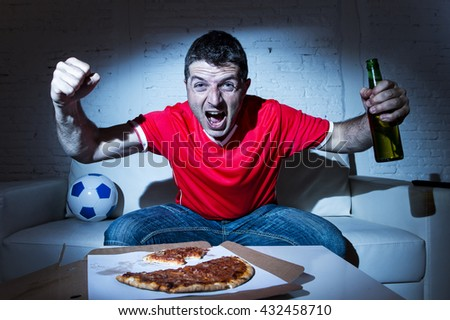 ecstatic and fanatic football fan man watching soccer game on television in red team jersey celebrating goal crazy happy on  couch at home with ball and  beer bottle eating pizza dark light set