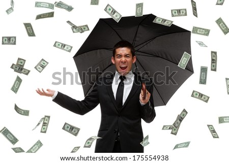 Ecstatic businessman holding an umbrella raining money.