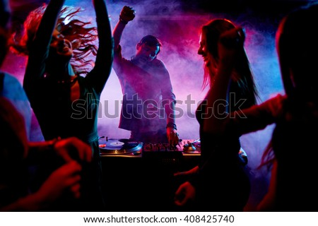 Ecstatic dj and dancers - stock photo