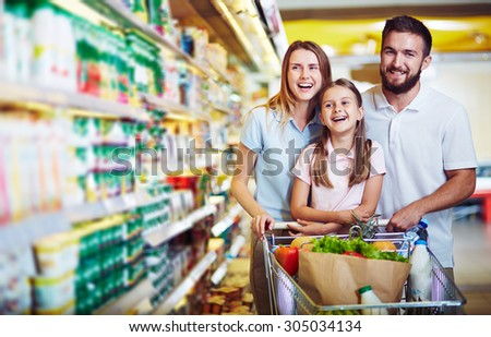 Ecstatic family with shopping cart with food visiting supermarket - stock photo