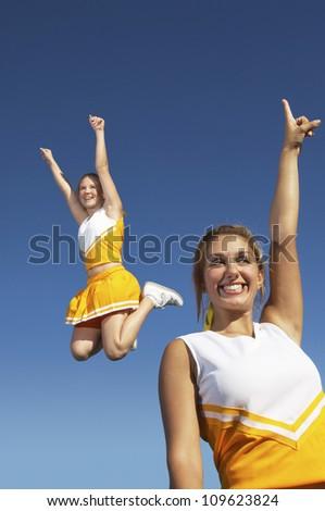 Ecstatic female cheerleaders against clear sky - stock photo
