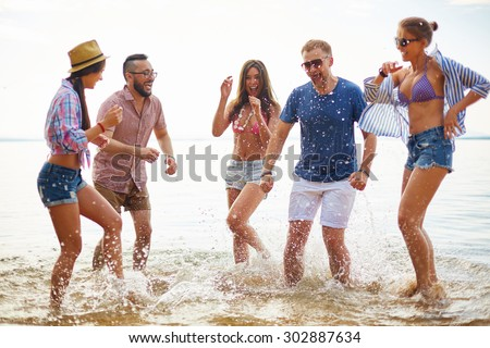 Ecstatic friends splashing water and laughing - stock photo