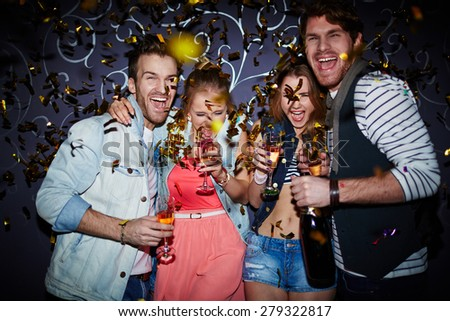 Ecstatic friends with champagne having fun at party