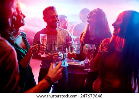 Ecstatic friends with champagne talking at party in night club - stock photo