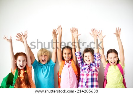 Ecstatic friends with raised arms looking at camera - stock photo