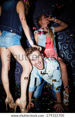 Ecstatic guy having fun with girls in night club - stock photo