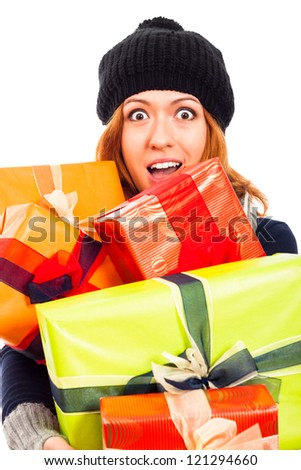 Ecstatic happy woman in winter hat holding many colorful gift boxes, isolated on white background. - stock photo