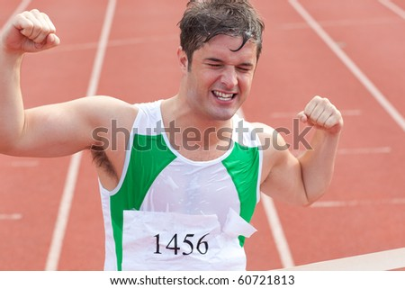 Ecstatic sprinter showing expression of victory in front of the arrival line in a stadium